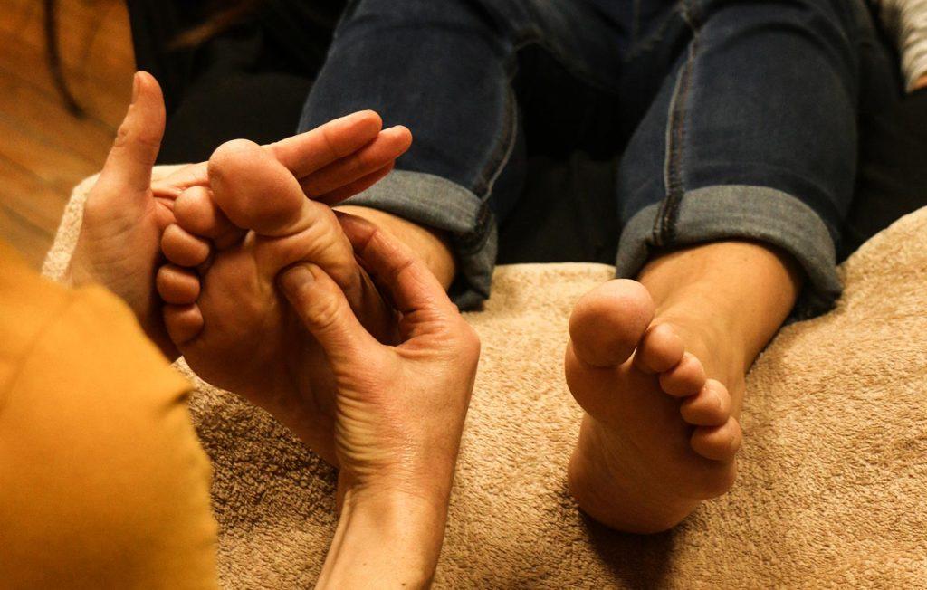 reflexologue-qui-masse-les-pieds-d-une-femme-enceinte