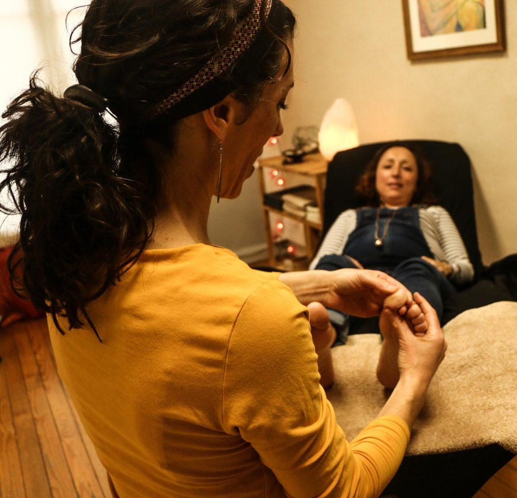une femme allongee et enceinte fait une seance de reflexologie